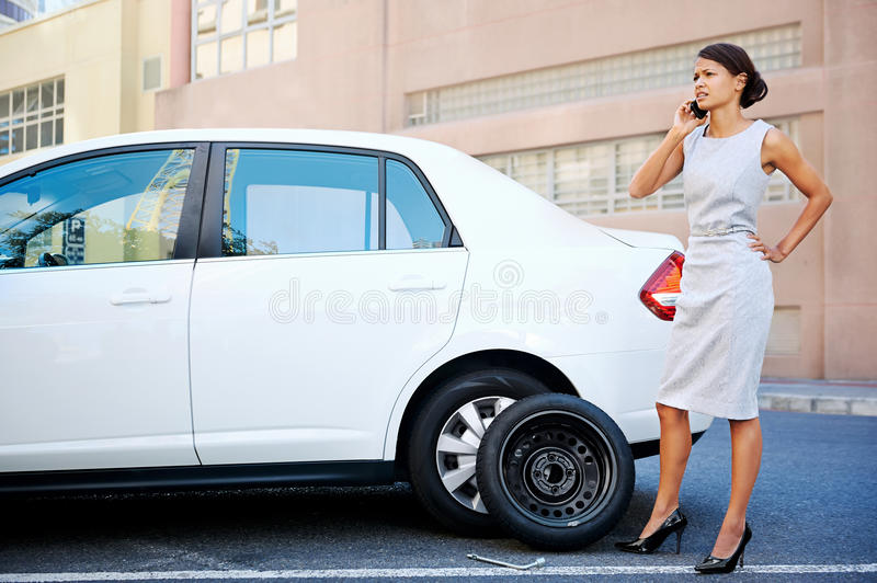 Businesswoman flat tire. Woman calling for assistance with flat tire on car in the city stock images