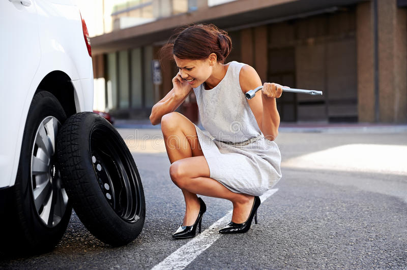 Businesswoman flat tire. Woman calling for assistance with flat tire on car in the city royalty free stock images