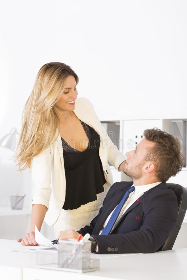 Businesswoman flirting with work colleague royalty free stock images