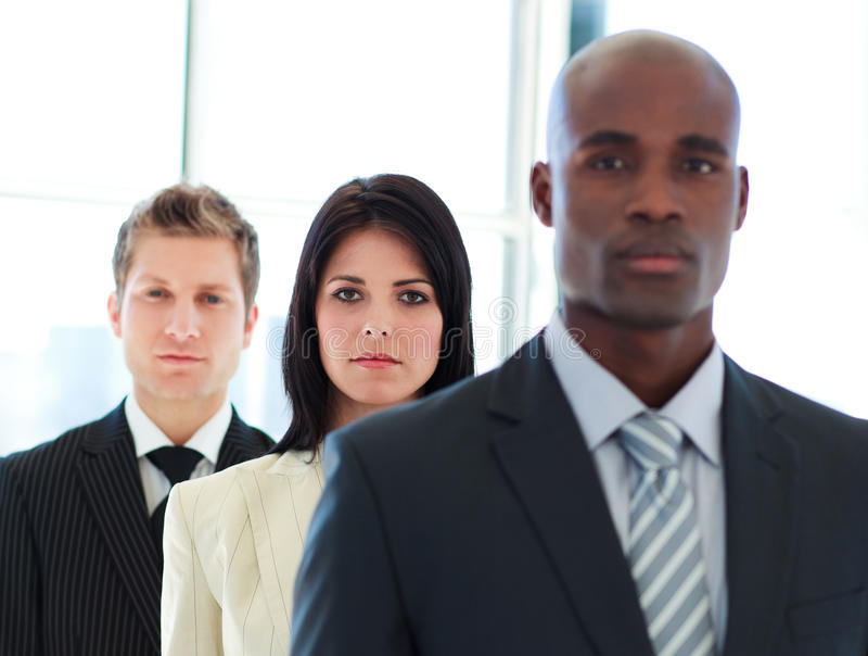 Businesswoman in focus with her team in a line. Serious brunette businesswoman in focus with her team in a line stock images
