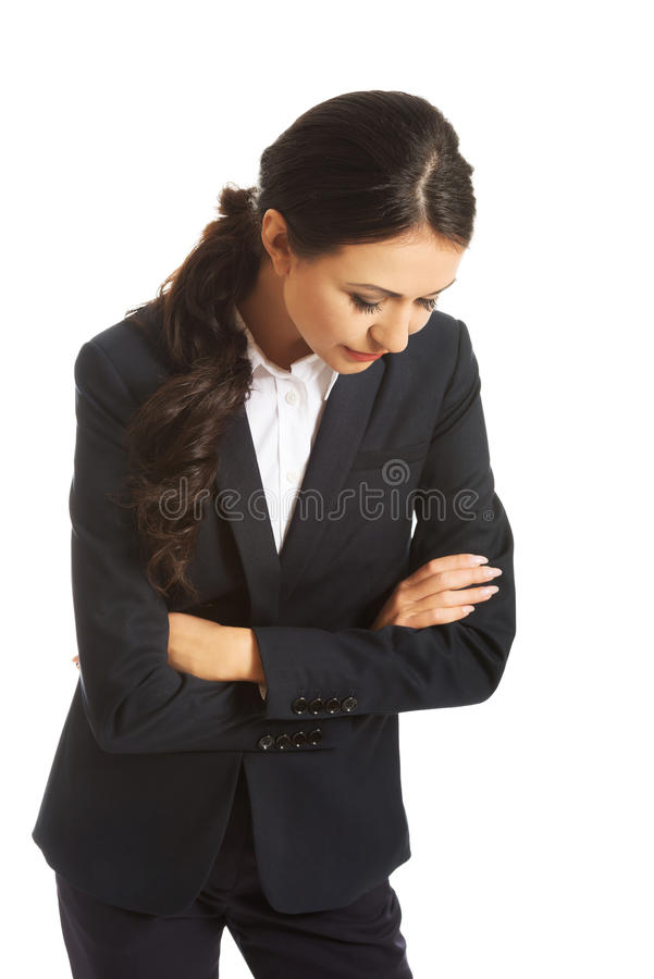 Businesswoman with folded arms looking down. Pensive businesswoman with folded arms looking down royalty free stock photos