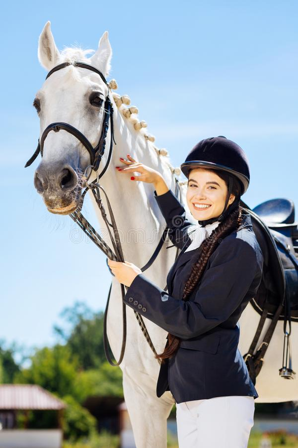 Businesswoman fond of equestrianism coming to race track. Fond of equestrianism. Beautiful smiling businesswoman fond of equestrianism coming to race track royalty free stock photography