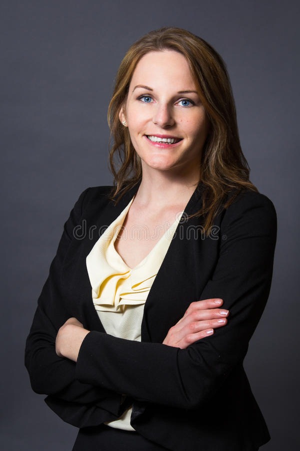Businesswoman in front of a grey background stock photos