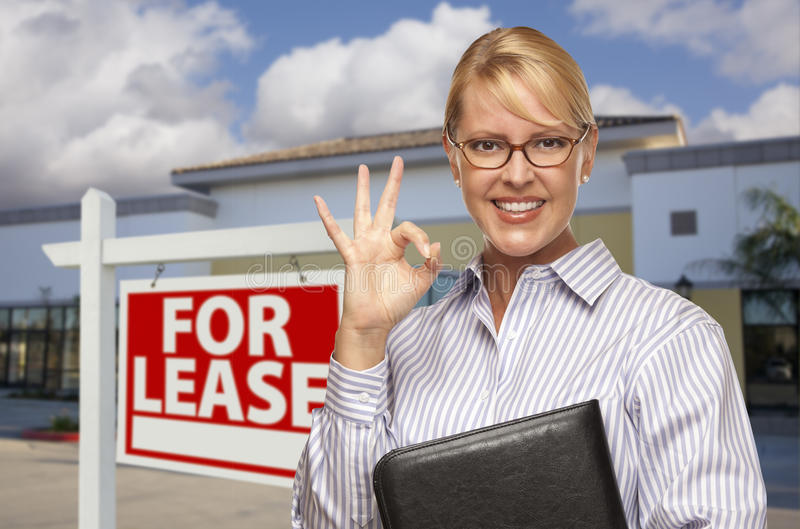 Businesswoman In Front of Office Building and For Lease Sign. Smiling Businesswoman with Okay Sign In Front of Vacant Office Building and For Lease Real Estate royalty free stock photography