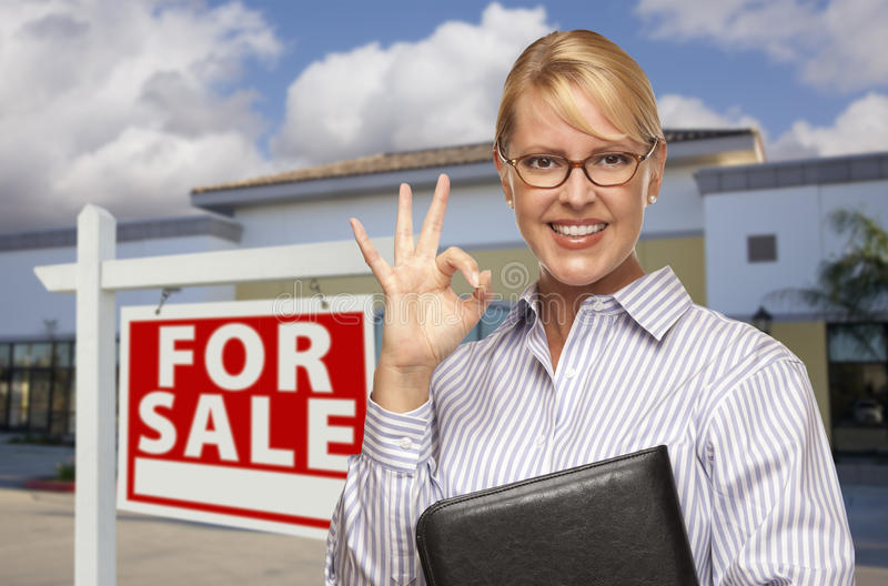 Businesswoman In Front of Office Building and For Sale Sign. Smiling Businesswoman with Okay Sign In Front of Vacant Office Building and For Sale Real Estate royalty free stock images