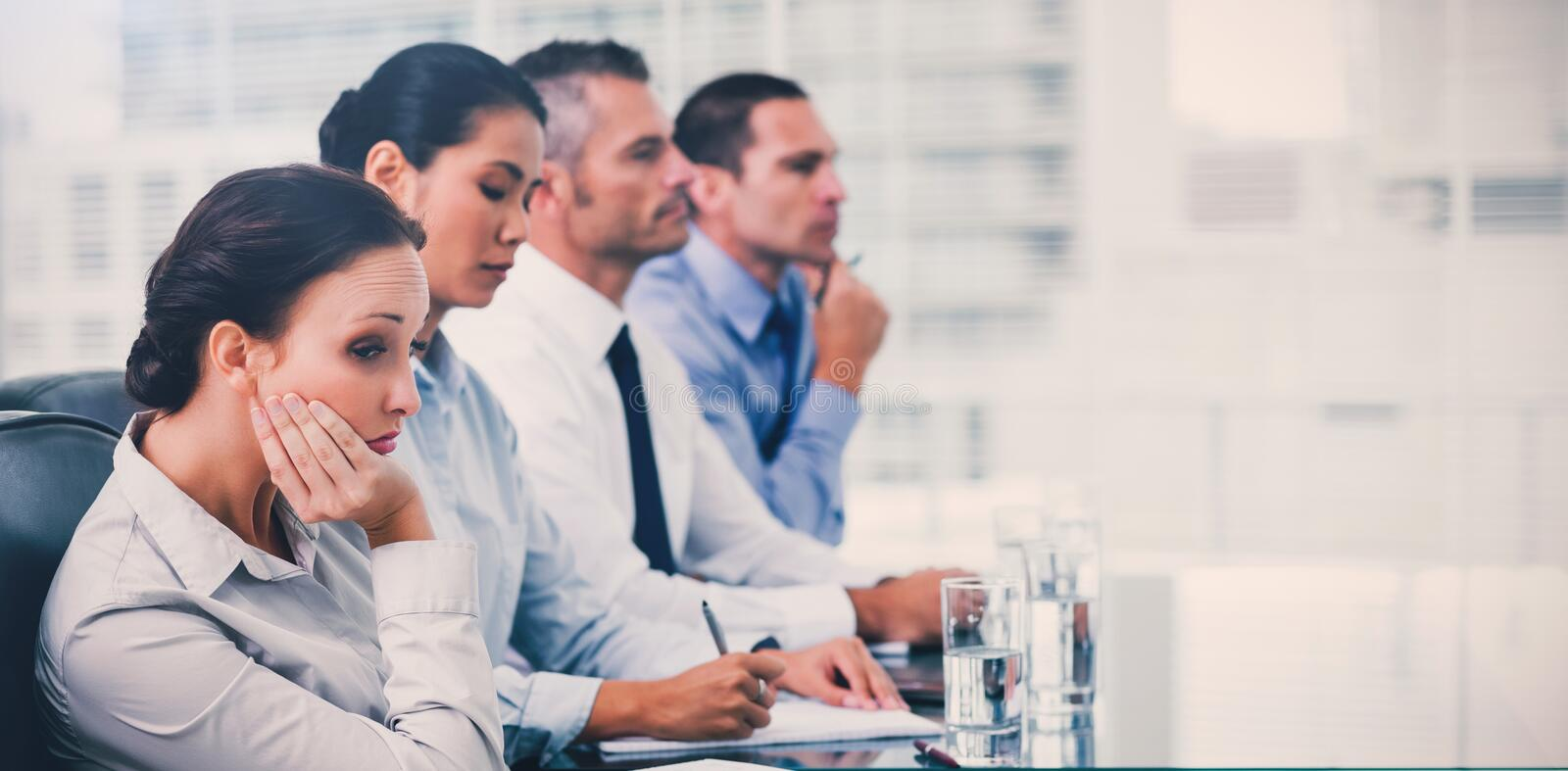 Businesswoman getting bored while attending presentation royalty free stock images