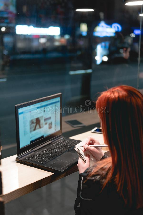 Businesswoman, girl holding a pen, writing in a notebook, laptop in cafe, smartphone, pen, use computer. Freelancer works remotely stock photo