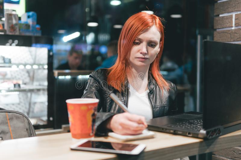 Businesswoman, girl holding a pen, writing in a notebook, laptop in cafe, smartphone, pen, use computer. Freelancer works remotely stock image