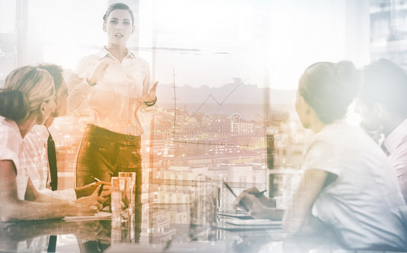 Businesswoman giving explication in front of a growing chart royalty free stock image