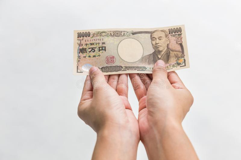 Businesswoman giving money and holding 10,000 japanese yen money in hand Isolated on white background, Japanese yen financial stock images