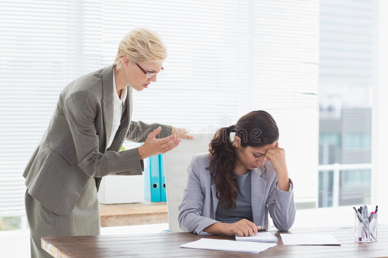 Businesswoman giving orders at her coworker. In an office royalty free stock photography