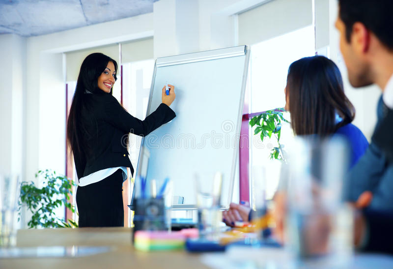 Businesswoman giving a presentation to colleagues stock images