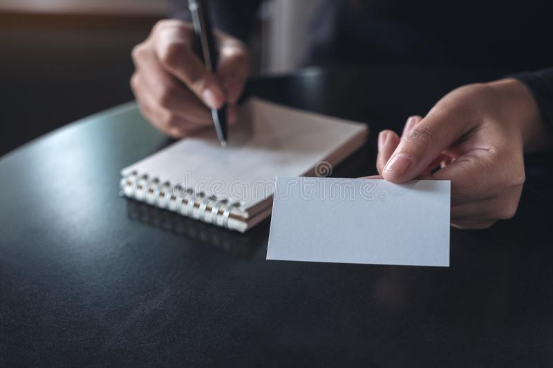 Businesswoman giving and showing an empty business card while writing down on notebook royalty free stock photos