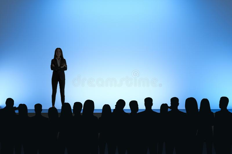 Businesswoman giving speech. In front of backlit audience on light blue background. Speaker and leader concept stock photography