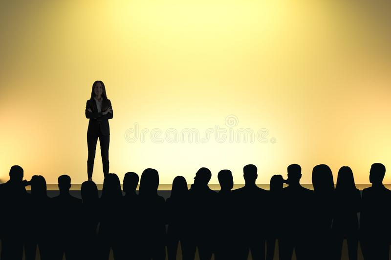 Businesswoman giving speech. In front of backlit audience on light yellow background. Speaker and motivation concept stock images