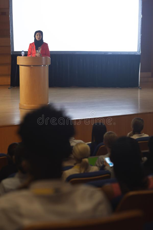 Businesswoman giving speech in front of audience in the auditorium stock image