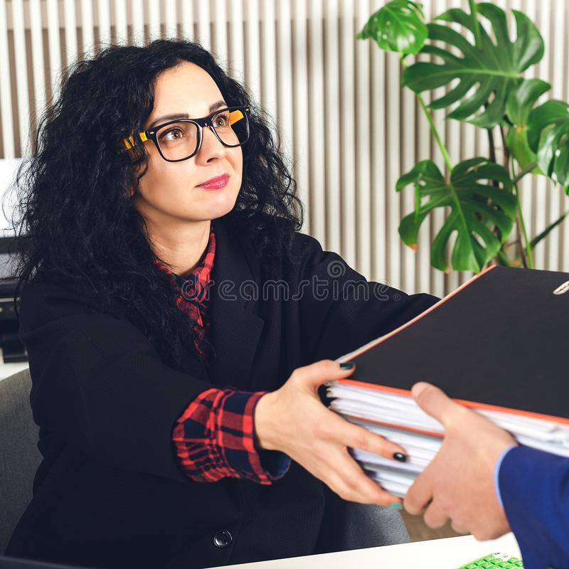 Businesswoman in glasses working at office with stack of folders. Female business partner needs to sign documents. Young woman at stock photography