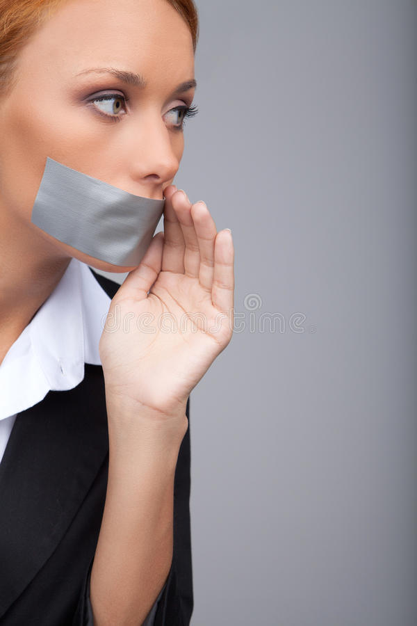 Businesswoman gossiping. Portrait of beautiful young businesswomen with her mouth covered with an adhesive tape standing isolated royalty free stock photos