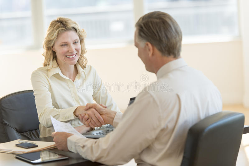 Businesswoman Greeting Colleague In Office stock photo