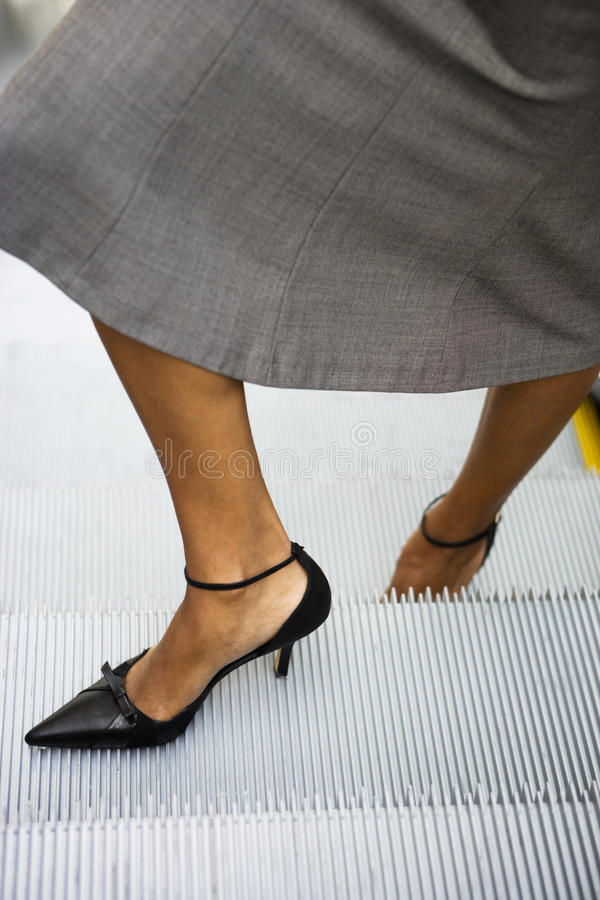 Businesswoman, in grey skirt and high heels, standing on escalator, close-up, low-section stock photos