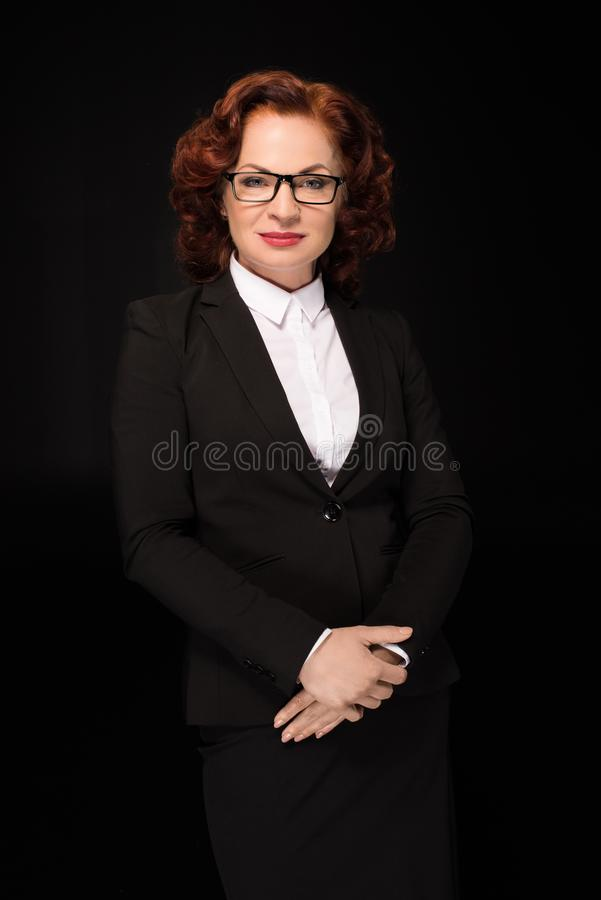 Businesswoman. Half-length shot of businesswoman in a suit posing with hands on her stomach and looking at camera royalty free stock photo
