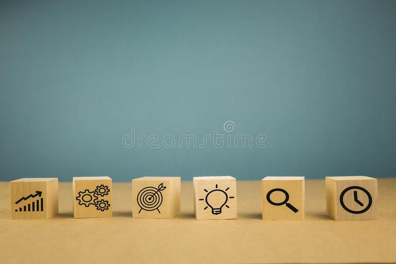 Businesswoman hand arranging wood block with icon business strategy and Action plan, copy space stock photography
