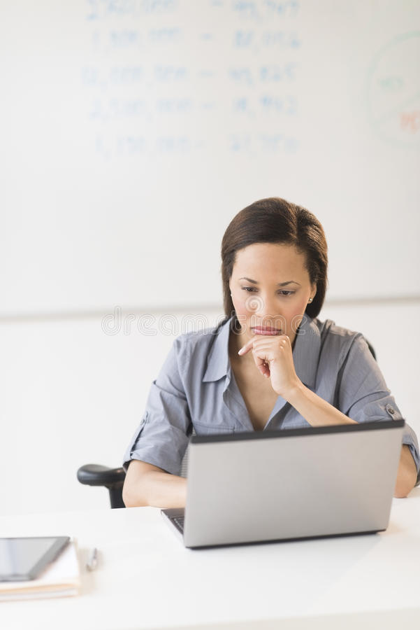 Download Businesswoman With Hand On Chin Using Laptop In Office Stock Photo - Image of occupation, office: 32429670