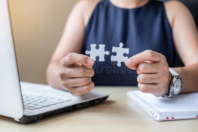 Businesswoman Hand connecting couple puzzle piece in office. Business solutions, mission, successful, goals and strategy concepts. Businesswoman Hand connecting stock photo