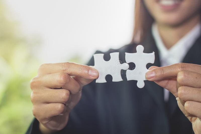 Businesswoman hand connecting jigsaw puzzle, Business solutions, success and strategy concept. stock photography
