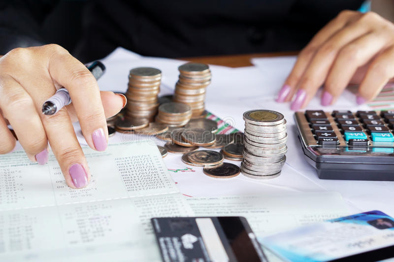 Businesswoman hand counting on saving account with stack of coins. Credit card and calculator stock photos
