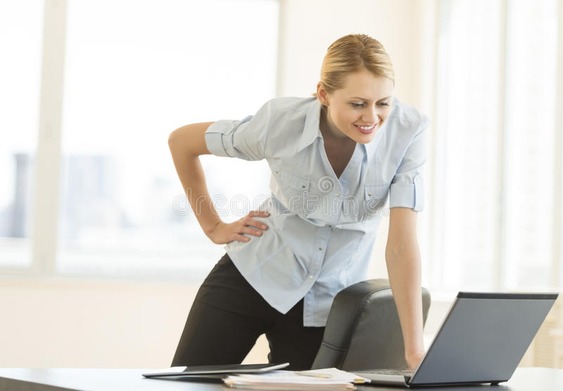 Download Businesswoman With Hand On Hip Looking At Laptop In Office Stock Image - Image: 32429805