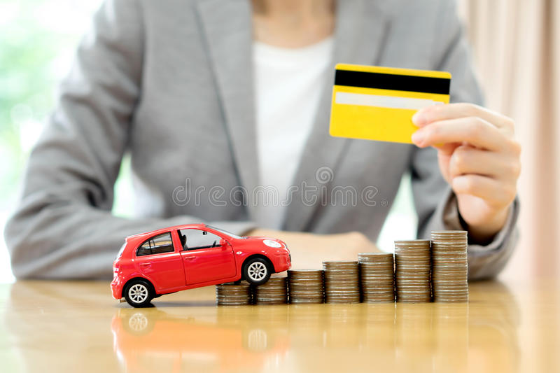 Businesswoman hand hold credit card, a toy car and a stack of co. Real estate investment by credit card. car and coins on the table stock photos