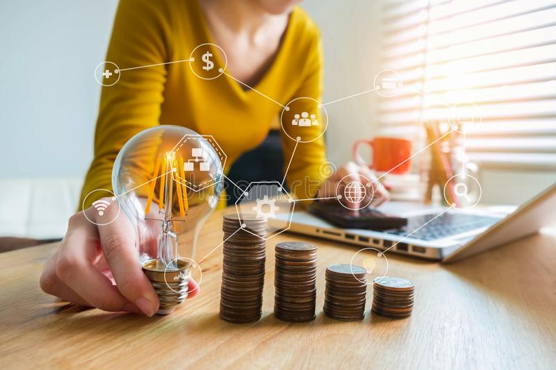 Businesswoman hand holding lightbulb with using calculator and laptop computer and money stack in office. royalty free stock images