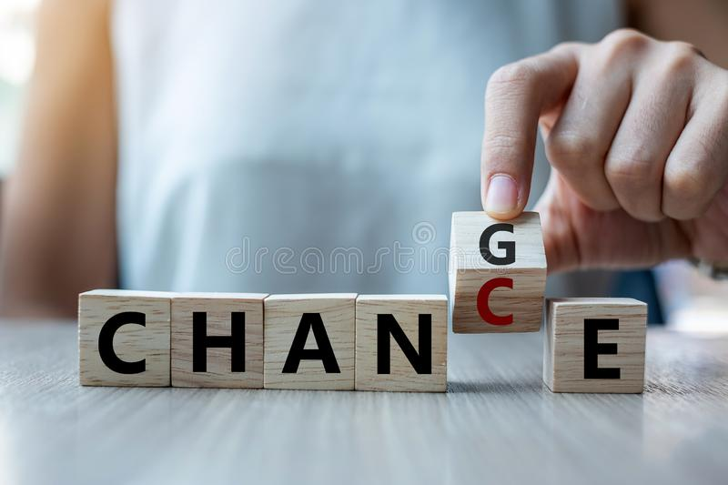 Businesswoman hand holding wooden cube with flip over block CHANGE to CHANCE word on table background. success, strategy, solution royalty free stock images