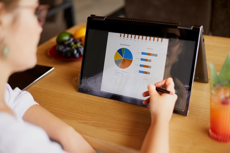 Businesswoman hand pointing with stylus on the chart over convertible laptop screen in tent mode. Woman using 2 in 1 stock photo
