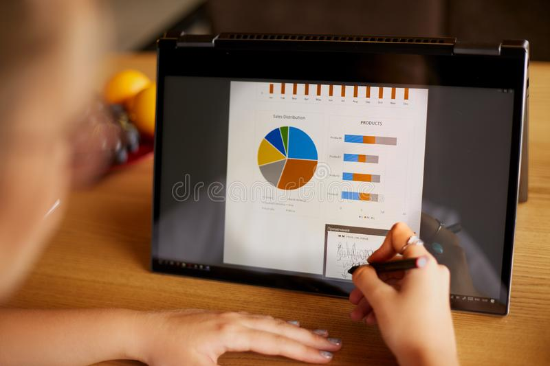 Businesswoman hand pointing with stylus on the chart over convertible laptop screen in tent mode. Woman using 2 in 1 stock images
