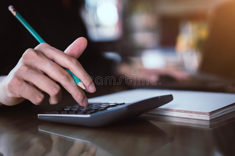 Businesswoman hand pressing on calculator for calculating cost estimating royalty free stock image