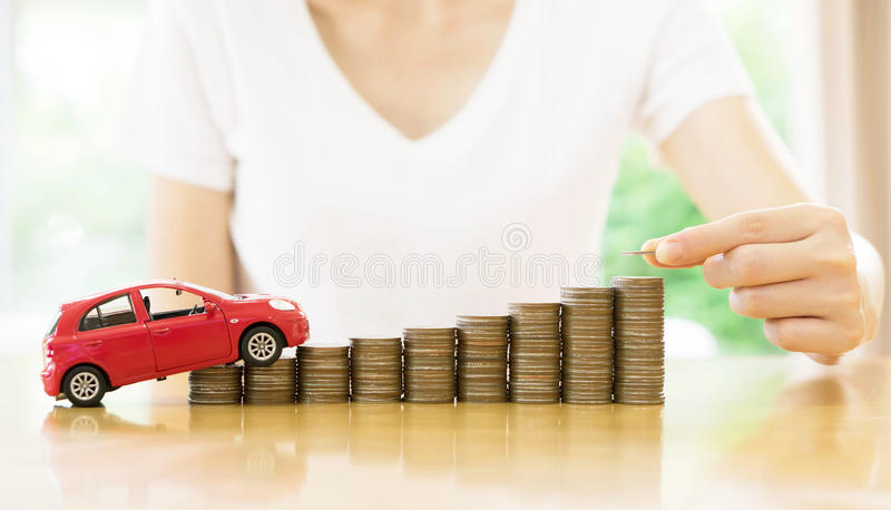 A Businesswoman hand pushing a toy car over a stack of coins. Businesswoman hand pushing a toy car over a stack of coins stock photos