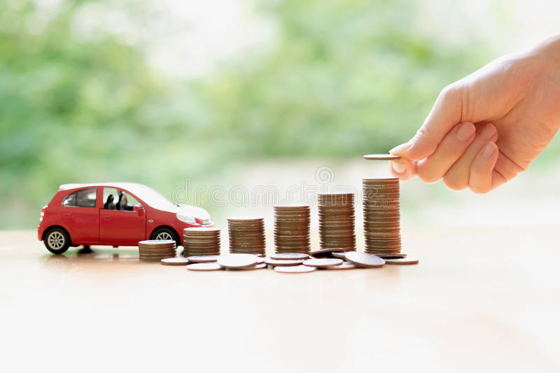 Businesswoman hand pushing a toy car over a stack of coins. A Businesswoman hand pushing a toy car over a stack of coins royalty free stock photos