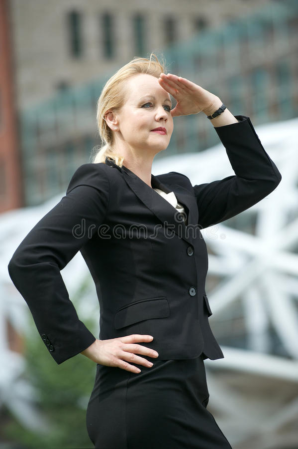 Businesswoman with hand to head salute in the city stock images
