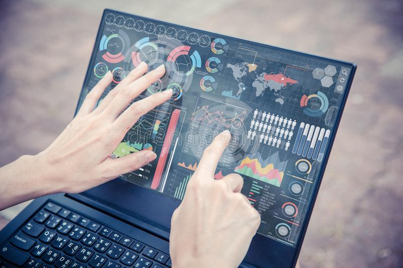 Businesswoman hand using advance technology computer touch screen business information data chart. Outdoor for decision support system royalty free stock image