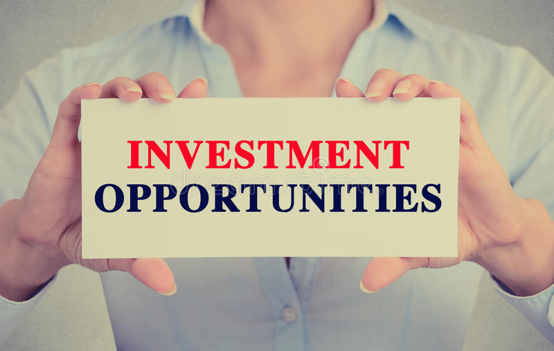 Businesswoman hands holding card with Investment Opportunities message royalty free stock photography