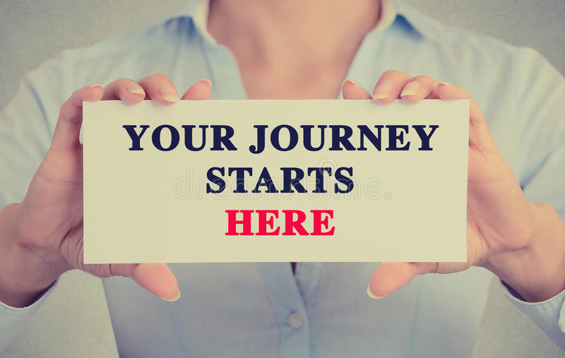 Businesswoman hands holding card sign with Your Journey Starts Here message stock photography