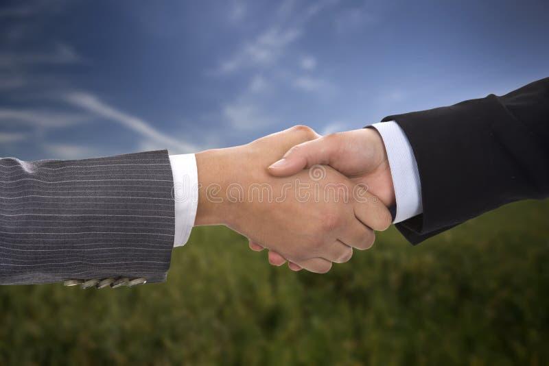 Businesswoman handshake over blurred background stock photo