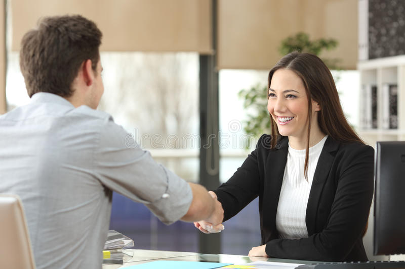 Businesswoman handshaking with client closing deal royalty free stock photography