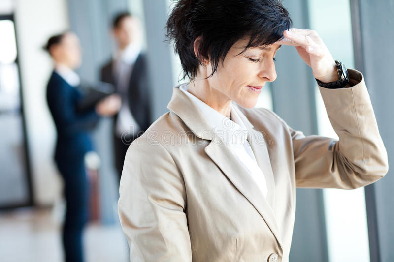 Businesswoman having headache. Middle aged businesswoman having headache in office royalty free stock photography