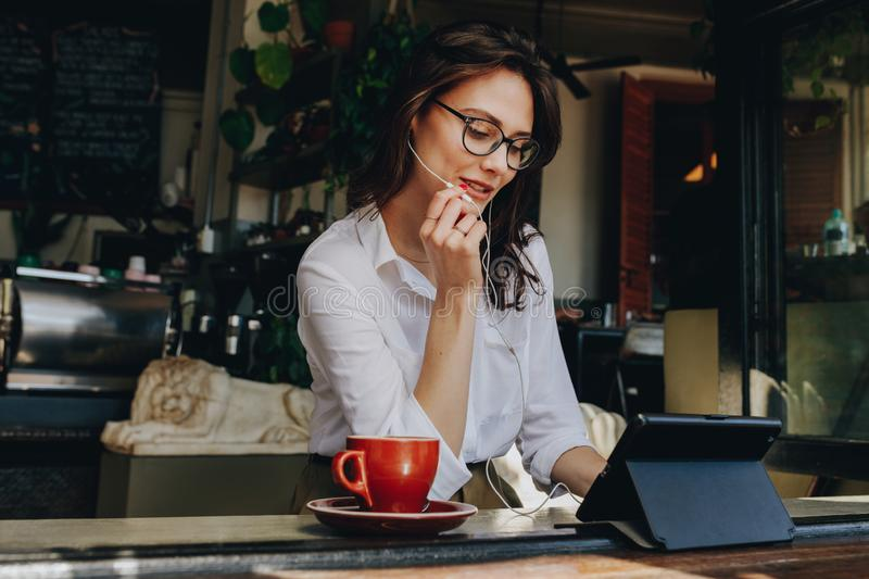 Businesswoman having a video chat on digital tablet while sitting at coffee shop. Female sitting at window table at cafe and stock photo