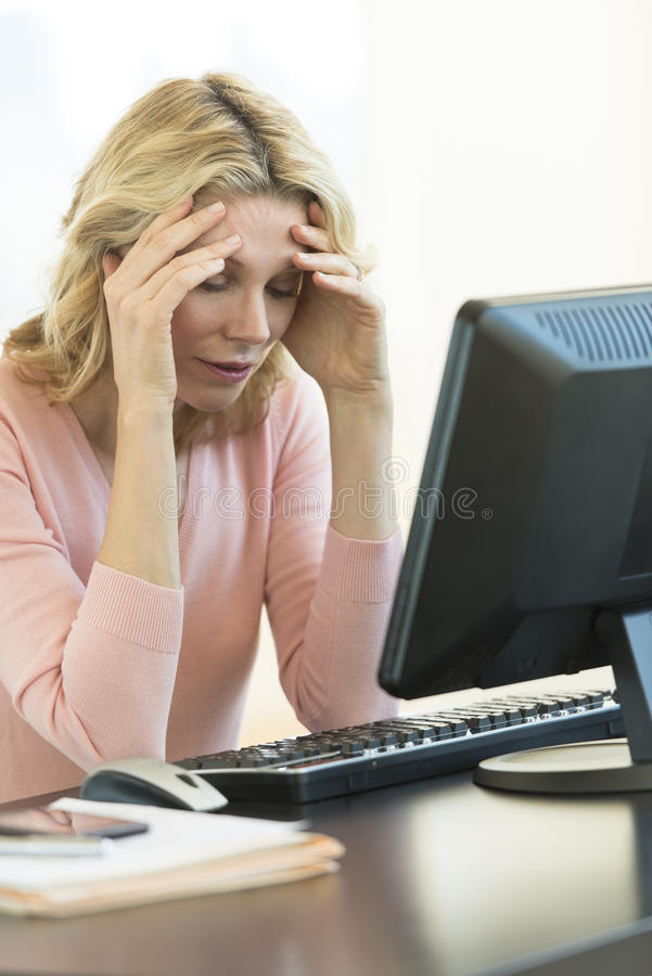 Download Businesswoman With Head In Hands Sitting At Desk Stock Image - Image: 32430157