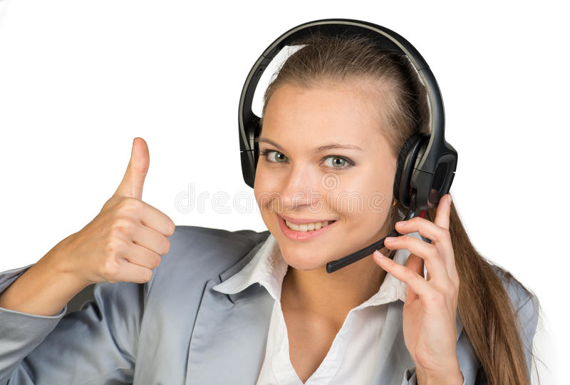 Businesswoman in headset showing thumb up. Her other hand on microphone boom, looking at camera, smiling. Isolated over white background royalty free stock photo