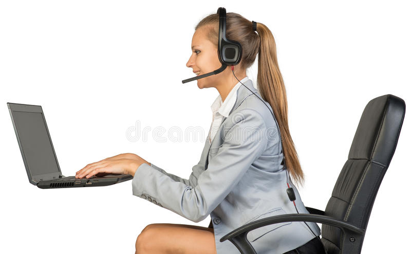 Businesswoman in headset, typing on laptop royalty free stock image